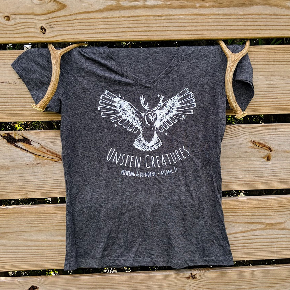 Front View of Women's T shirt in dark grey with unseen creatures logo in white on center of chest hung on a wooden fence with decorative antlers