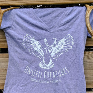 Close up Front View of Women's T shirt in grey with unseen creatures logo in white on center of chest hung on a wooden fence with decorative antlers