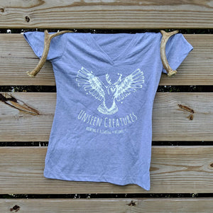 Front View of Women's T shirt in grey with unseen creatures logo in white on center of chest hung on a wooden fence with decorative antlers