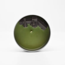 Load image into Gallery viewer, The surface of the Manderley-Scented Candle features a wax mansion overlooking a wax ocean.