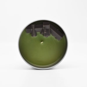 The surface of the Manderley-Scented Candle features a wax mansion overlooking a wax ocean.