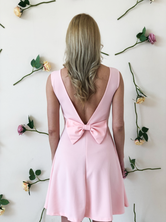 blonde-girl-wears-pink-dress-with-a-bow-back-side