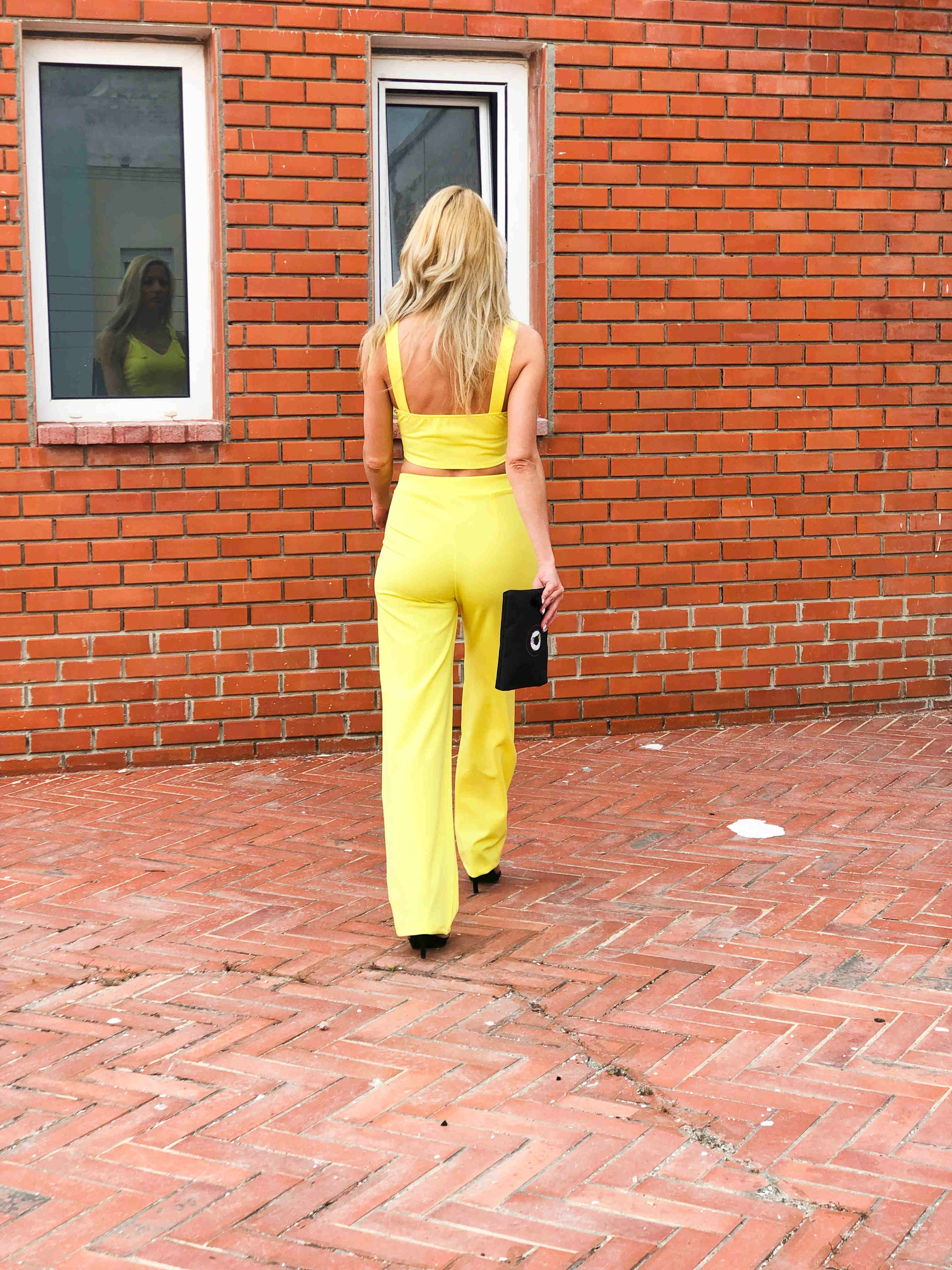 blonde-girl-wears-yellow-crop-top-and-trouser-backside