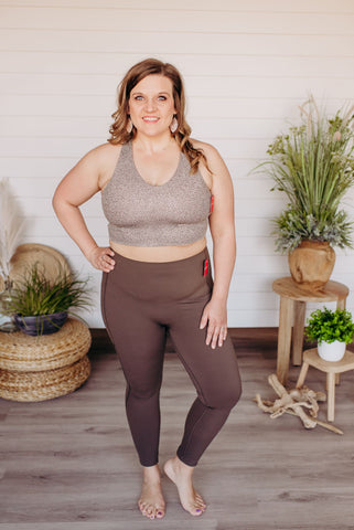 Woman models the spanx activewear plus size leggings in bark color. She stands with her hand on her hip and is smiling.