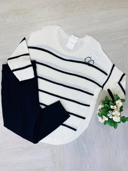 flat lay display of a black and white striped sweater and leggings. Zoom call outfit inspiration for Plus Size Women