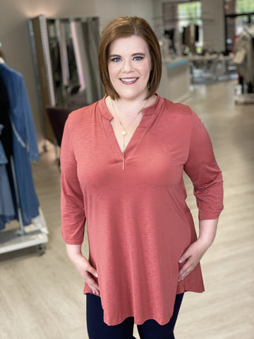 Woman smiling while wearing peach blousy tunic top