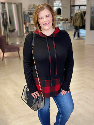 Woman smiles while wearing a black and buffalo check hoodie paired with skinny jeans.