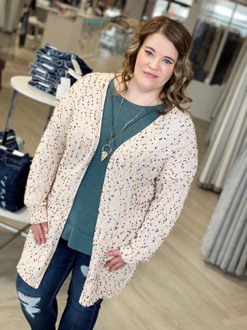 Wearing wears cardigan with dusty blue top and high rise plus size jeans.