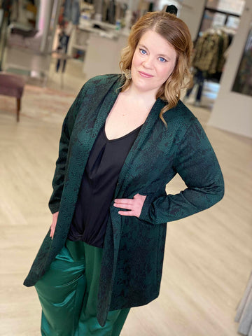 Woman smiles while wearing a snake print emerald long jacket, black tee and silky emerald joggers.