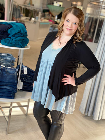 Smiling woman models Faux Leather Leggings paired with a long, lacey tank and a black open front cardigan.