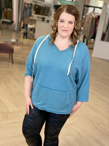 Smiling woman models SPANX faux leather leggings with a jewel blue hooded sweatshirt with white drawstrings.