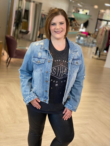 """A smiling woman models faux leather SPANX leggings paired with a graphic tee that says, """"Love as I have loved you"""" and a distressed jean jacket."""