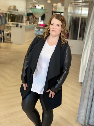 woman models faux leather SPANX leggings and a long draped black jacket paired with a plain white tee.