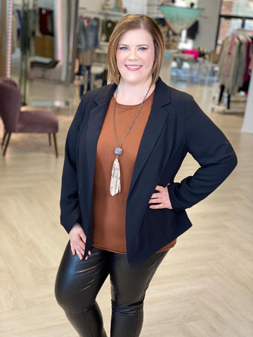 woman models SPANX Faux leather black leggings paired with a caramel colored sweater and a business professional black blazer.