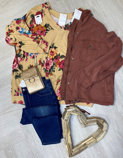 flat lay of a mauve jacket, yellow floral top and skinny jeans for a plus size zoom call outfit idea.
