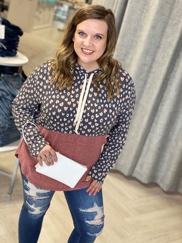 woman smiles while holding a white clutch and wearing a valentines day hoodie