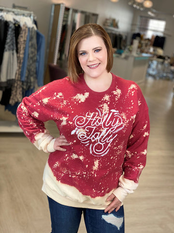 woman smiling while wearing a graphic sweatshirt that says holly jolly.