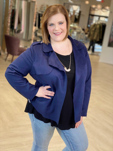 Woman stands with hand on hip wearing a blue suede jacket and jeans.