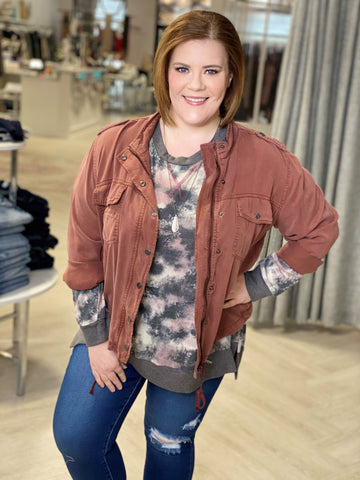 Love Marlow Boutique model stands wearing a dusty rose bomber jacket, tie dye shirt and jeans making a stylish plus size outfit.
