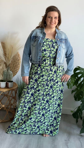 Woman stands wearing a green and blue maxi dress paired with a denim jean jacket. she is modeling a plus size maxi dress.