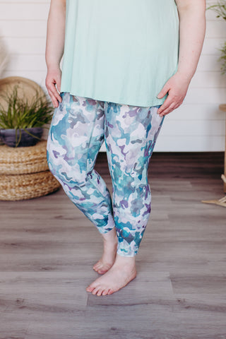 Woman stands with her hands at her waist showing off the new Spanx Leggings in Blue Camo