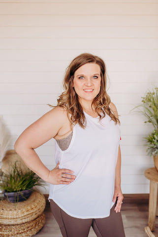 Woman stands with her hand on her hip showing off the new Spanx Tank top in white.