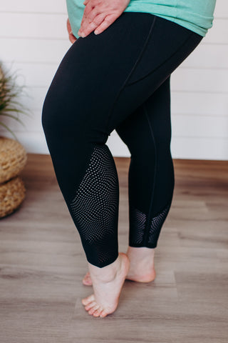 Woman stands with her knee popped to show off the laser cuts in the new black Spanx Activewear plus size leggings.