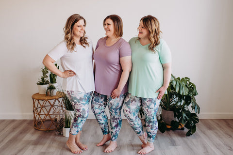 3 woman stand smiling while wearing matching Spanx Blue camo leggings and different colored plain tees.