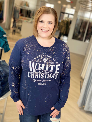 woman smiling wearing a dark blue graphic tee that says I'm dreaming of a white christmas.