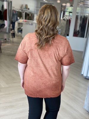 Back of plus size graphic tee in mineral wash burnt orange.
