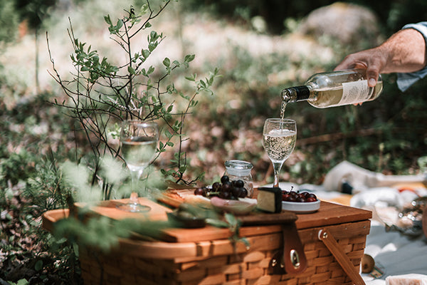 Pouring a glass of wine at a picnic.