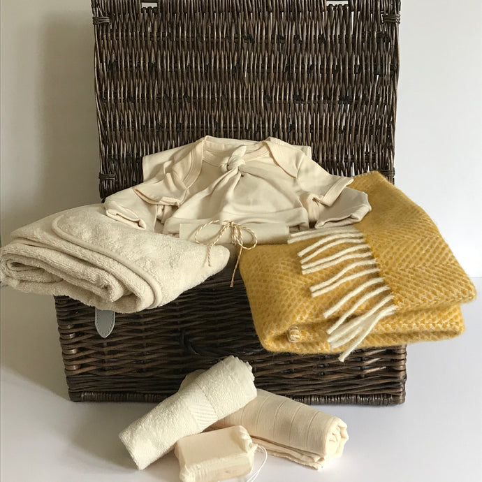 Rory & Ruby celebration baby hamper filled with organic and eco-friendly welcome to the world gifts with beehive gold pure new wool pram blanket.