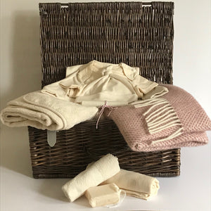 Rory & Ruby celebration baby hamper filled with organic and eco-friendly welcome to the world gifts with dusky pink pure new wool pram blanket.