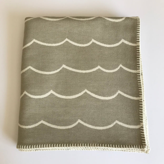 Rory & Ruby reversible wave design throw in sand and ivory with traditional blanket stitch edging.
