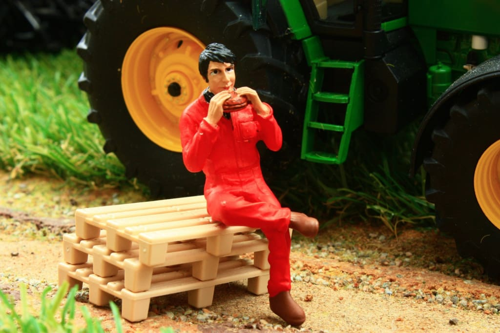 AT32128 AT COLLECTIONS FARMER SITTING EATING SANDWICH