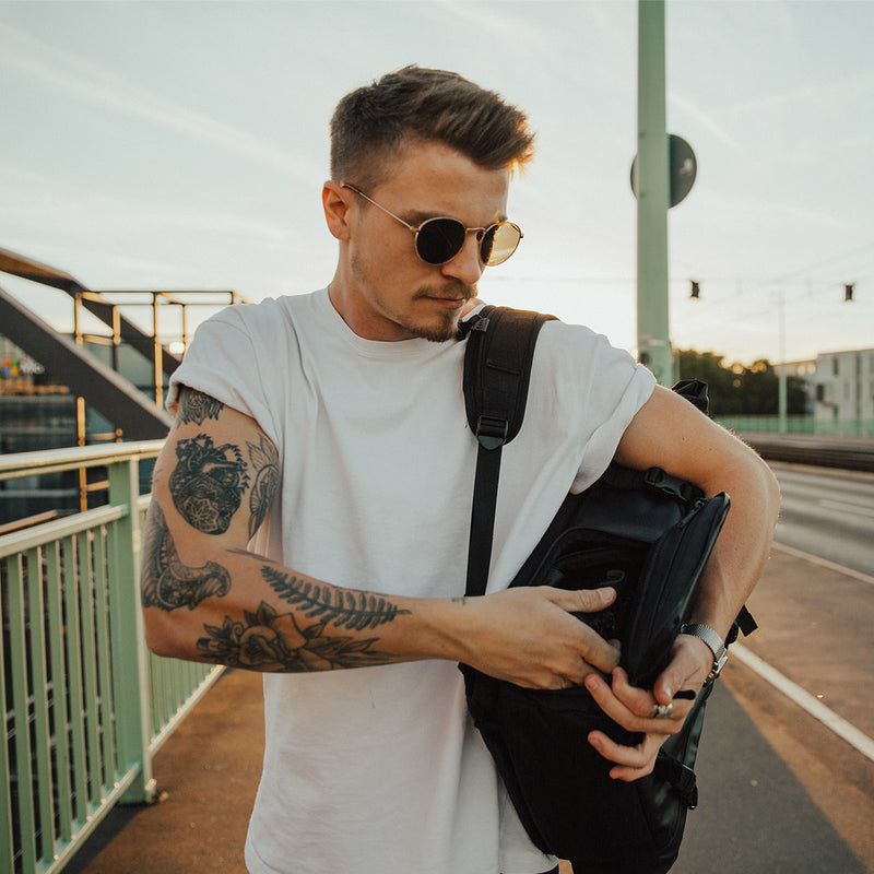 Man taking a camera from WANDRD PRVKE 31L Black backpack