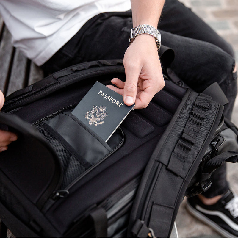Man taking passport from WANDRD PRVKE 31L Black backpack