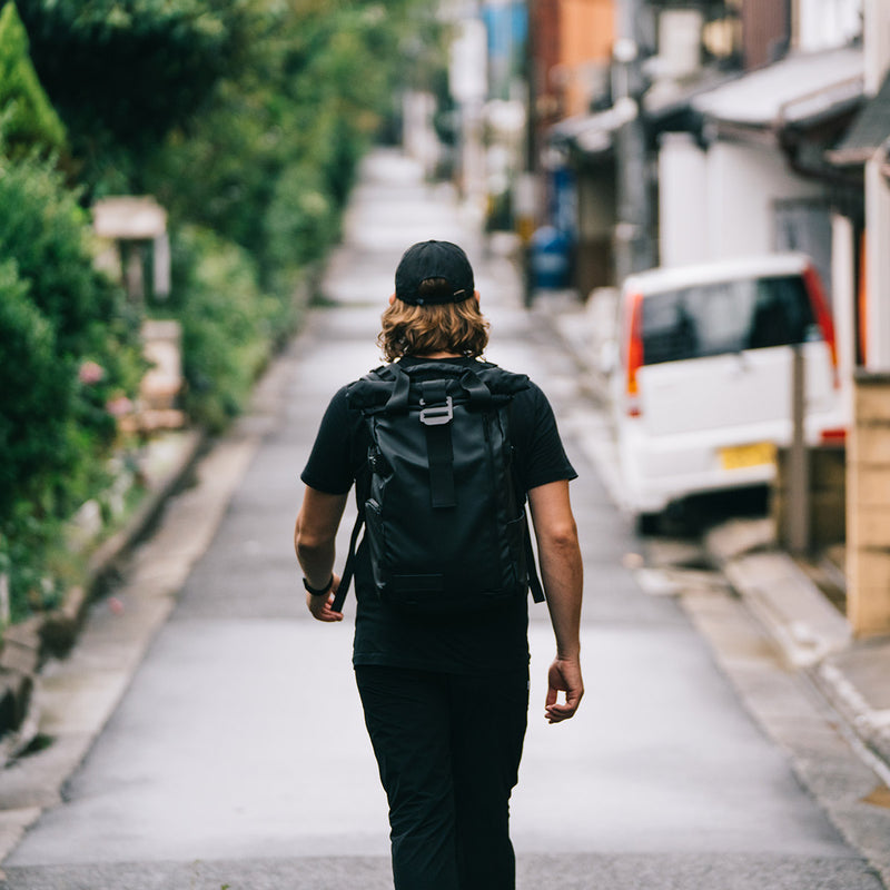 Man walking in a street with WANDRD PRVKE 31L Black backpack