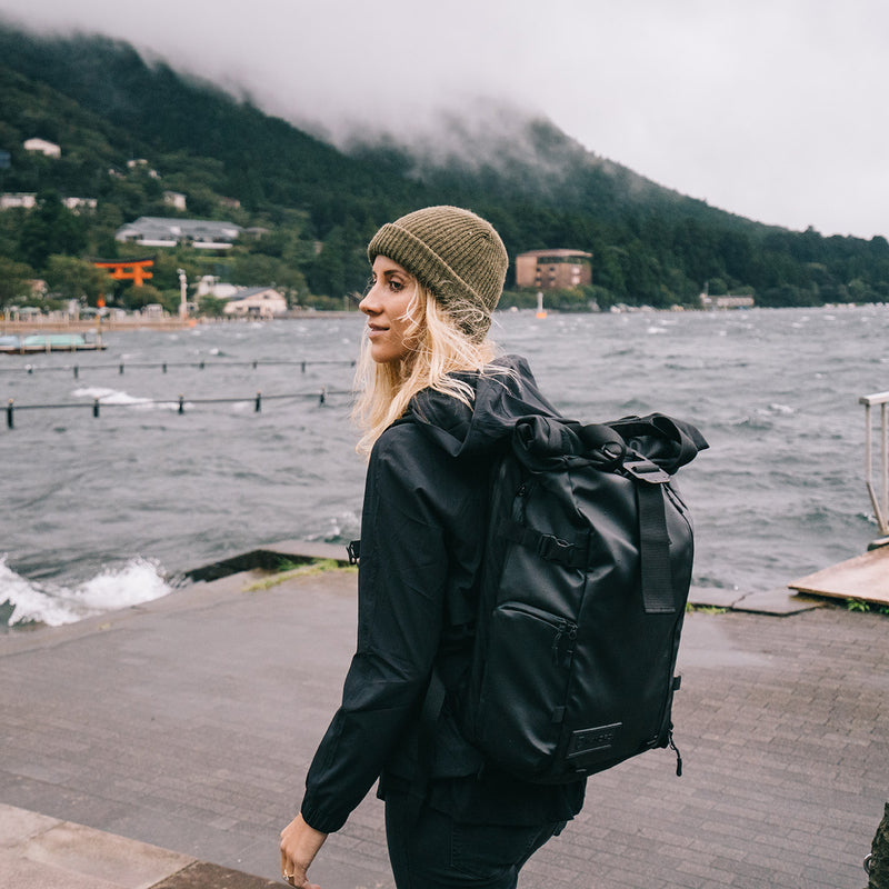 Woman carrying WANDRD PRVKE 31L Black backpack on a beach