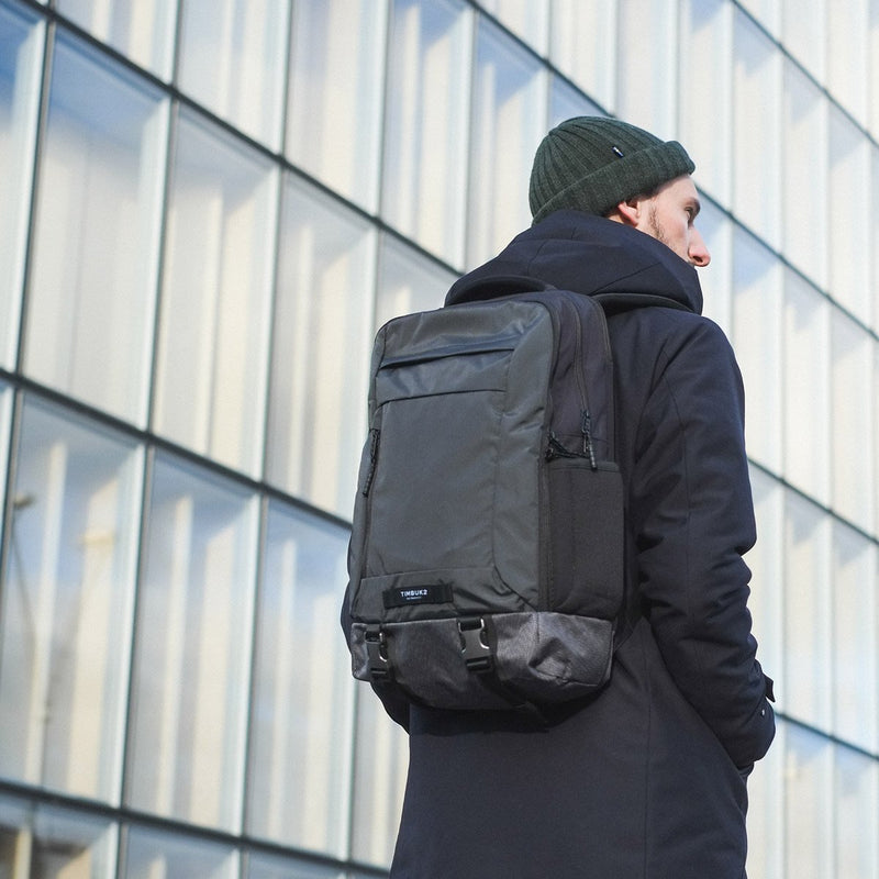 Man walking next to tower with TImbuk2 Authority Twilight Backpack