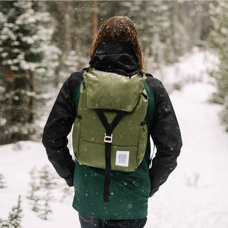Topo Designs Y Pack Olive on a man in the forest under the snow