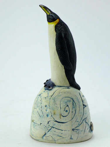 Small ceramic penguin on a hill with blue base