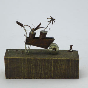 Wheelbarrow with plants on wooden base
