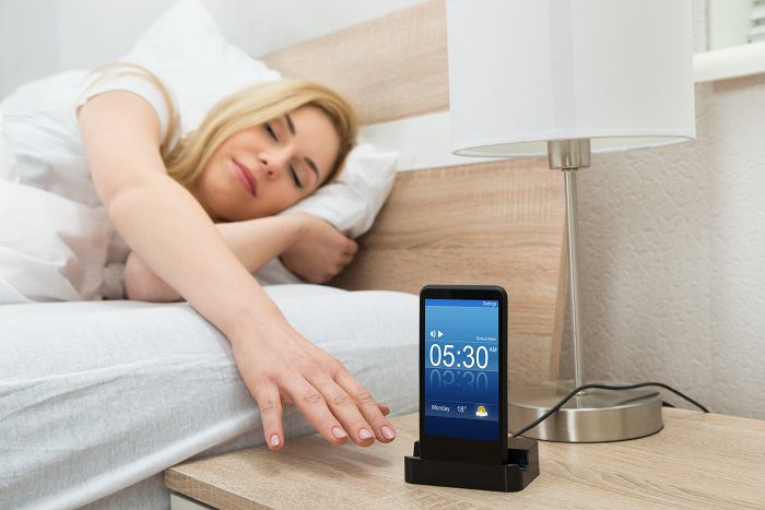 Woman reaching out to bedside alarm clock