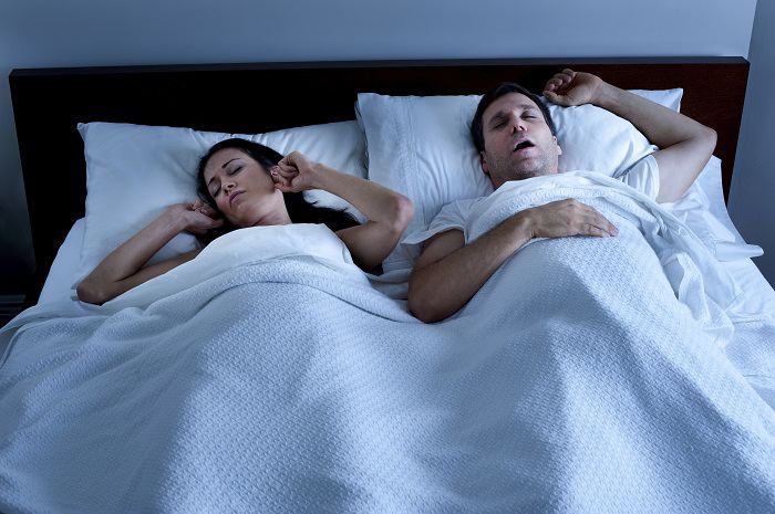 Woman puts fingers in ears as a man snores in bed
