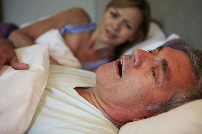 Man snoring in bed as woman looks disgusted