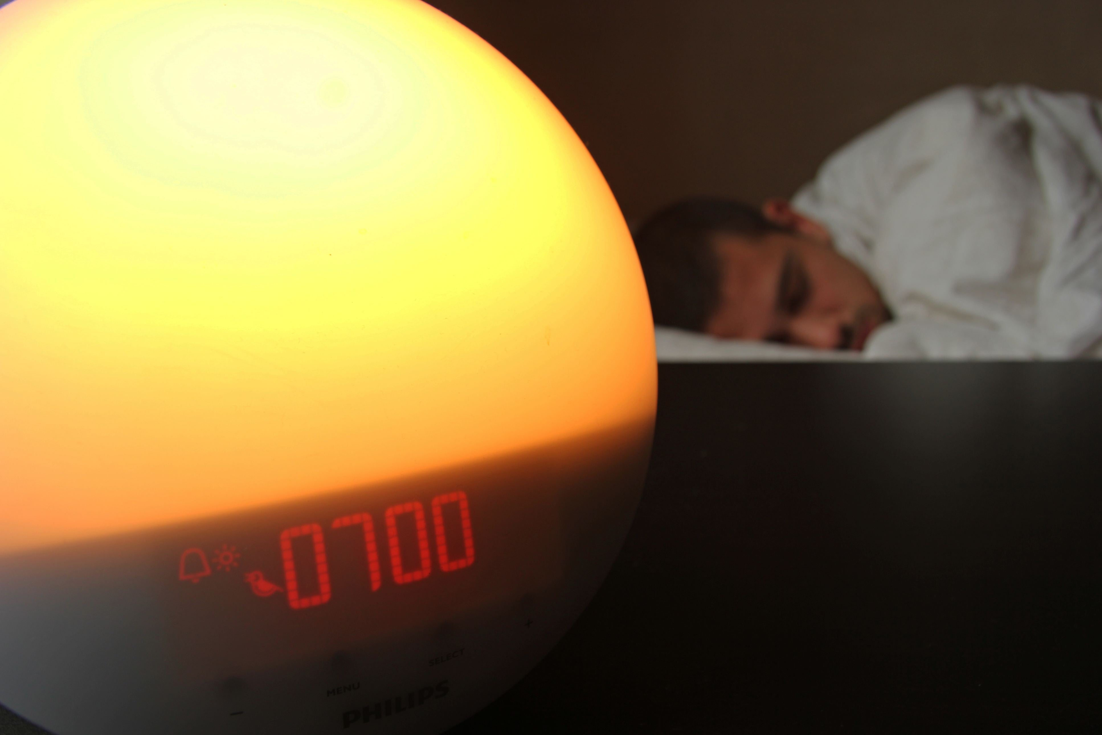 Man alsleep in bed with Alarm clock in foreground