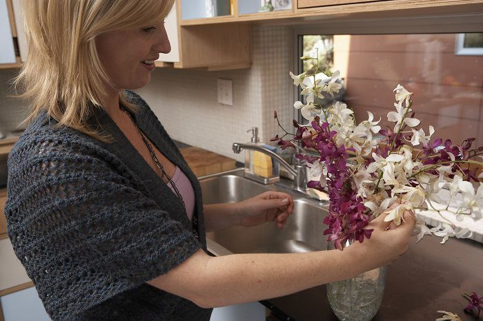 Woman arranging flowers in a vase in the kitchen