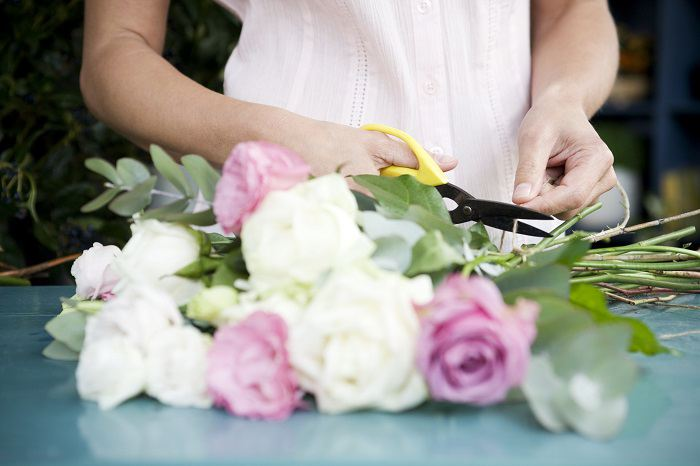 Woman arranging and trimming flowers