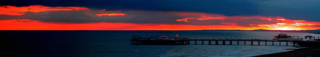 Sunset over the sea showing Brighton and The West pier (PRINT)